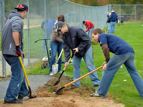Volunteers work on one of four baseball fields at River's