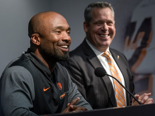 In this photo taken Oct. 9, 2017, Oregon State Vice President and Director of Athletics Scott Barns, right, and interim football coach Cory Hall attend a news conference in Corvallis, Ore., after head football coach Gary Andersen agreed to mutually part with the university. (Andy Cripe/The Corvallis Gazette-Times via AP)