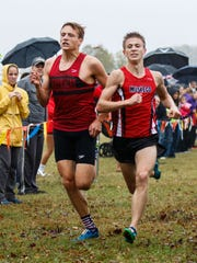 Muskego senior Gino Pierangeli narrowly edges out Arrowhead's Cody Clauer for fifth place in the Classic 8 Conference Championship cross country meet at Lake Denoon Middle School in Muskego on Saturday, Oct. 14, 2017.