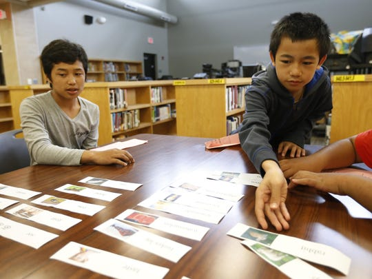 Soe Thu, right, helps sort state fair-related vocabulary words into different categories June 25, 2015, during an English Language Learners summer school program at Meredith Middle School in Des Moines.