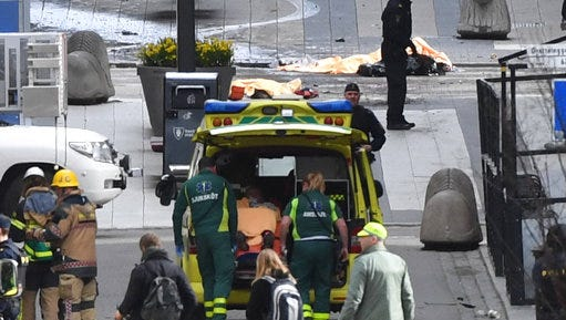 """Emergency personnel load a person into an ambulance, centre, at the scene after a truck crashed into a department store injuring several people in central Stockholm, Sweden, Friday April 7, 2017.  Swedish Prime Minister Stefan Lofven says everything indicates a truck that has crashed into a major department store in downtown Stockholm is """"a terror attack."""""""
