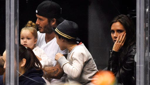 FILE - In this Saturday, April 12, 2014 file photo, David Beckham, second left, sits with his daughter, Harper, son, Cruz, and wife Victoria, watch the Los Angeles Kings play the Anaheim Ducks in Los Angeles. Harper Beckham is only 5 years old, but her famous mother already is taking steps to protect her brand. Fashion designer and former Spice Girl Victoria Beckham has registered daughter Harper's name with intellectual property authorities in Britain and Europe, it was announced Thursday, April 13, 2017.