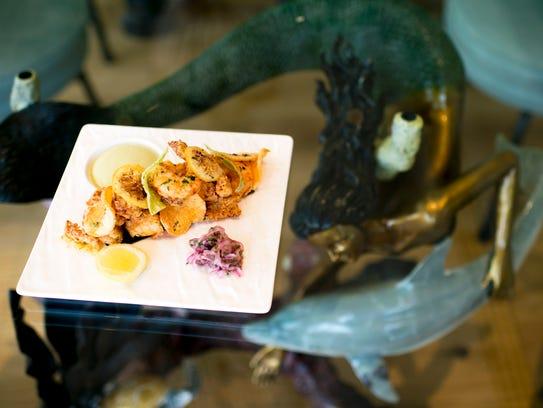 A mixed fish fry dish with calamari, mahi mahi, shrimp,