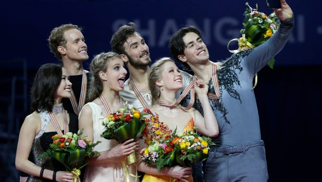 Gold medal winners Gabriella Papadakis and Guillaume Cizeron of France, center, silver medal winners Madison Chock and Evan Bates of the U.S. (and Novi) and bronze medal winners Kaitlyn Weaver and Andrew Poje of Canada (and the Detroit Skating Club) pose for a selfie during the ice dance award ceremony of the ISU World Figure Skating Championships at Shanghai Oriental Sports Center in Shanghai, China, on March 27, 2015.