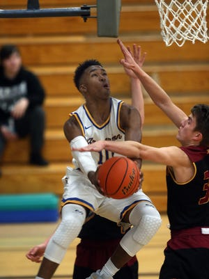 Bremerton's Japrea Pedesclaux cuts under the basket for a reverse defensed by KingstonÕs Liam Young, left,Tuesday night at Bremerton.