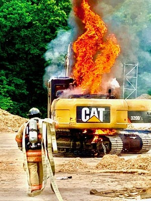 Flames erupted Wednesday afternoon in the engine compartment of an excavator at E.L. Harvey & Sons Inc. in Hopkinton. The piece of heavy equipment was destroyed.