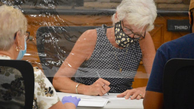 Workers count mail-in ballots submitted for a special election in late August at Holland City Hall.