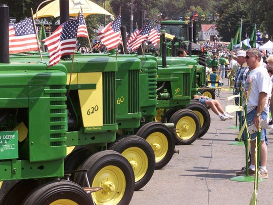 Iowa State Fair visitors look over a gleaming row of vintage two-cylinder John Deere tractors on the Grand Concourse one afternoon in 2000.
