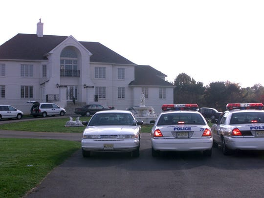 Police cars (above) are among the vehicles in the driveway of the Bluebell Road, Colts Neck, home where two penny stock promoters were murdered 15 years ago. Investigators (below, left) carry files and computer parts from the home. On the day of his funeral, mourners (below, right) place the casket of Maier Lehmann — one of the murder victims — in a hearse.