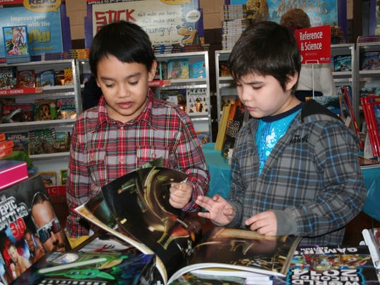 In this file photo from 2014, Randolph Ochoa and Derick Lira glance through a science-themed book at a Scholastic Book Fair at St. Gregory School in St. Nazianz.