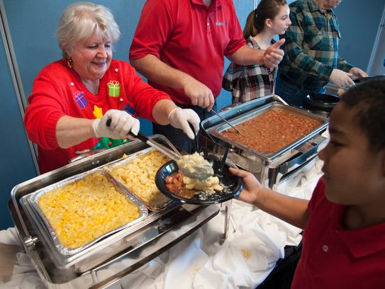 Volunteer Sue King of Williamstown, left, serves food