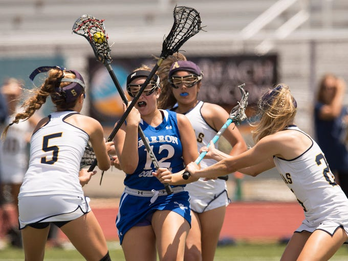 Barron Collier's Jaclyn Berry (center) brings the ball