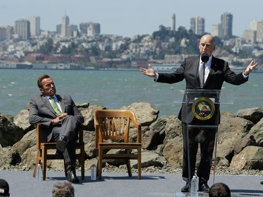 California Gov. Jerry Brown gestures while speaking as former Gov. Arnold Schwarzenegger listens before the signing of a climate bill on Treasure Island on July 25, 2017, in San Francisco.