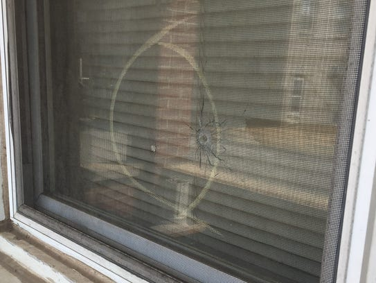 A bullet hole is visible in the front window of a rowhome