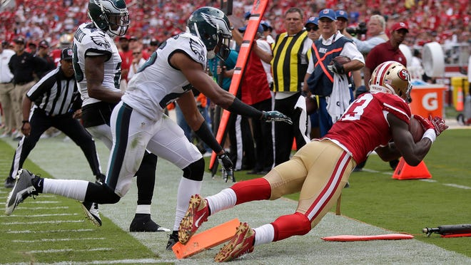 49ers wide receiver Steve Johnson (right) catches a 12-yard touchdown pass next to Eagles cornerbacks Cary Williams (center) and Nolan Carroll during the third quarter of Sunday's game.