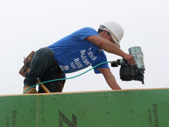 A volunteer builder prepares the top walls for tresses on a new home in Wyoming on Tuesday that will be used as a residence for AmeriCorps members serving with Central Delaware Habitat for Humanity and other local nonprofits.