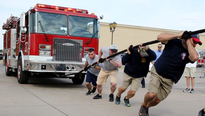The Wichita Falls Fire Department dig in to pull the fire truck during the Special Olympics Texas - North Texas Area 9 annual Fire Truck Pull Saturday, Sept. 16, 2017, in the Academy parking lot. Five teams entered the contest with the Wichita Falls Fire Department winning the men's division and the Flames winning the women's division.