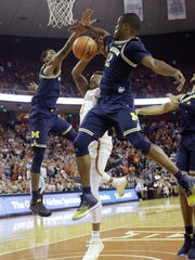 Texas guard Jacob Young (3) is blocked as he drives to the basket between Michigan defenders Charles Matthews (1) and Muhammad-Ali Abdur-Rahkman (12) during the second half U-M's 59-52 win on Tuesday, Dec. 12, 2017, in Austin, Texas.