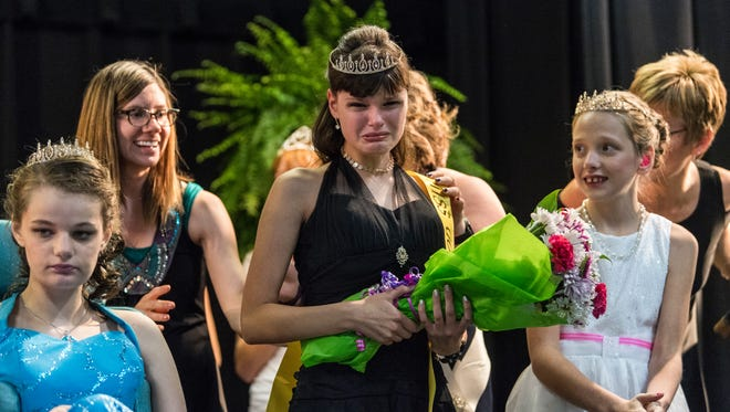 "Heather Benford (center) cries after being crowned Miss Golden during the 2017 pageant. Standing on the stage with Benford, Megan James (left) was awarded ""Most Princess Like,"" and Shelby Buckwinkel (right) was awarded ""Best Smile."""