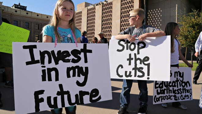 Siblings, Ashley Kistner,6 Justin Kistner, 10, and Natalie Kistner, 8, hold signs during a protest against Governor Ducey's proposed educational budget cuts at the state capital. Their mother, Brooke Kistner, was one of the rally's organizers as seen in Phoenix on Feb., 25, 2015