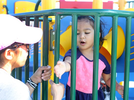 Noelle Mathew, age 3, of Middletown, got a little help escaping the playground jail from her mother Michelle on Wednesday at the new Can-Do Playground at Charles E. Price Memorial Park on Level Roads in Middletown.