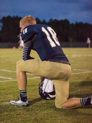 Holy Trinity?s starting quarterback/defensive back Daniel Welch (18) takes a breather while the special teams are on the field.  (  Prep Sports )