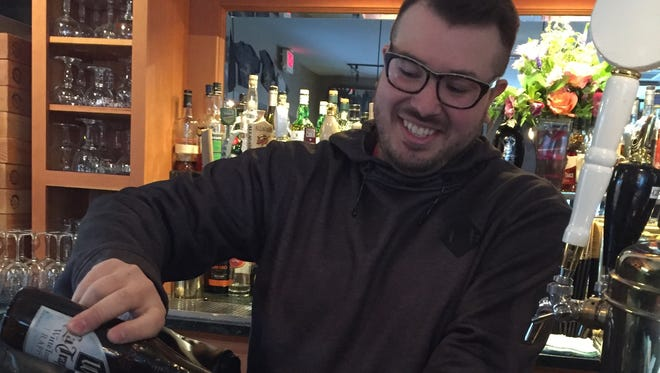 Farmhouse Tap & Grill barman Justin Gould pours a La Trappe Witte, a non-spiced Trappist wheat beer.