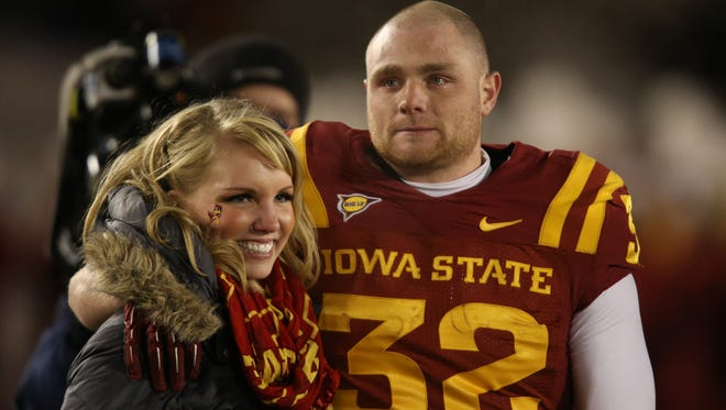 Iowa State running back Jeff Woody and his wife, Hannah, walk onto the field during senior night introductions prior to kickoff against Kansas Nov. 23, 2013 at Jack Trice Stadium in Ames.