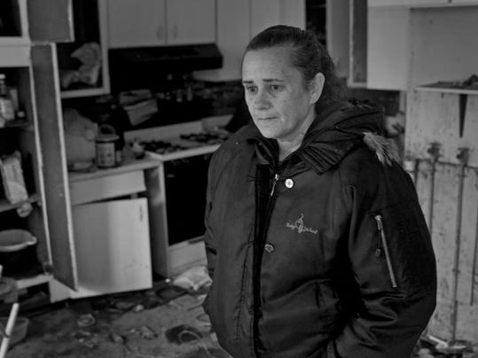 Joyce Bornemann, of Union Beach, surveys her ruined home one block from the beach. The night the storm hit, she