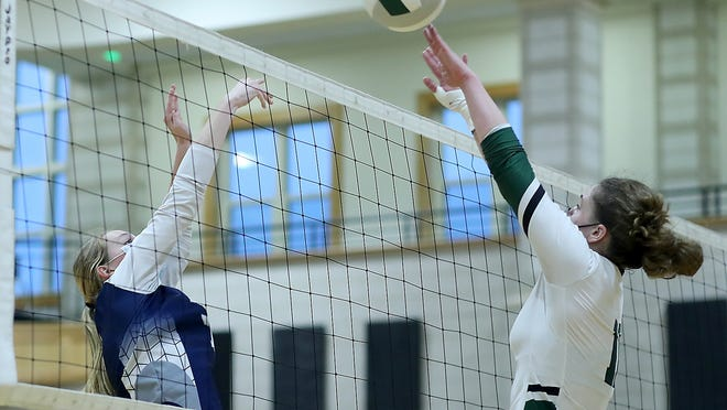 Plymouth North's Mandy Drew and Marshfield's Allison Majenski meet at the net during second set action of their match on Oct. 13.