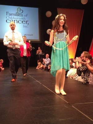 Amelia Gorton, a survivor of childhood cancer, holds her Bravery Beads as she models during the 2016 Prevea Runway for Life, a fashion-show fundraiser held at Jet Air at Austin Straubel International Airport.