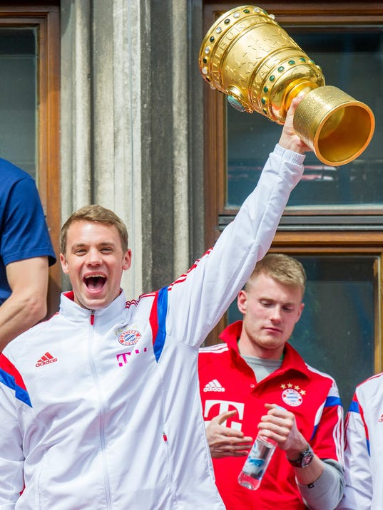 Bayern Munich's   goalie Manuel Neuer  celebrates the club's  Cup title with teammates on the balcony of the city hall in Munich, Germany,  Sunday May 18, 2014. Munich won the final of the German soccer Cup  against Borussia Dortmund  on Saturday. (AP Photo/dpa, Marc Mueller)
