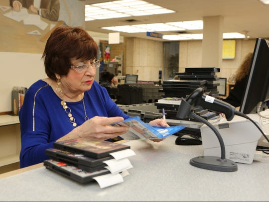 Clerk Betsy Sodano checks in materials that were left