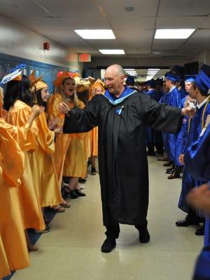 Retiring Principal Thomas Calder  congratulates senior class members at his last graduation ceremony at Spotswood High School.