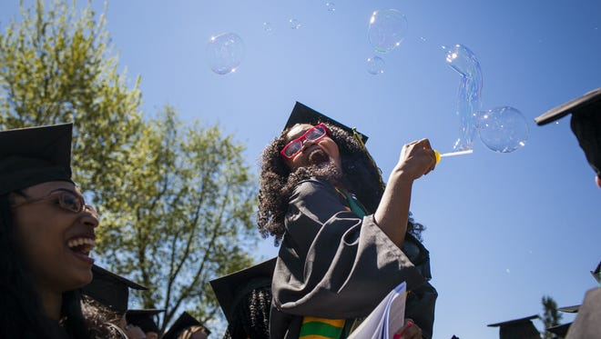 University of Vermont graduate Mache Chase blows bubbles after the 2014 commencement on the University Green in Burlington on Sunday. Chase was one of three students who received the Elmer Nicholson Achievement Prize.
