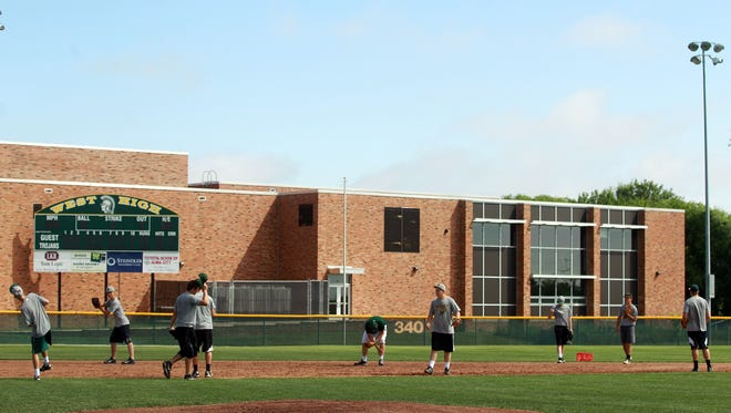 West High baseball players practice Friday behind their school. District leaders have recently discussed where athletics practices and games could take place if a new high school in North Liberty opens early.