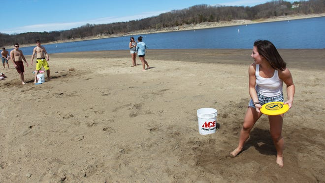 University of Iowa junior Hannah Wickberg tosses a frisbee as she enjoys the warm weather with friends at the Coralville Lake beach on Friday, April 25, 2014. David Scrivner / Iowa City Press-Citizen