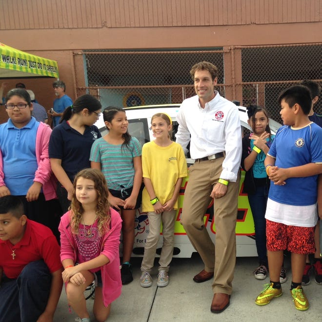 A yellow-shirted Janella Hassel, winner of Florida's 2014 Walk to School poster contest, stands by NASCAR driver Scott Lagasse at Bonita Springs Elementary Monday.