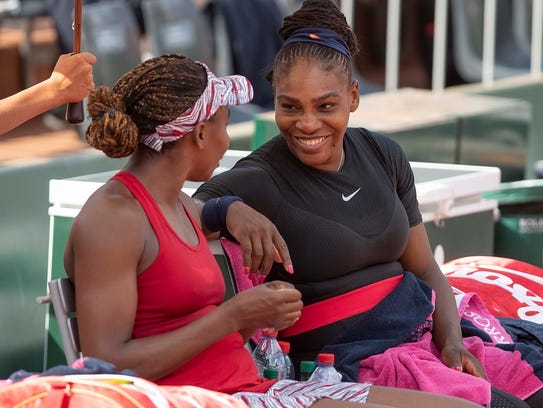 Venus Williams (left) and Serena Williams share a moment
