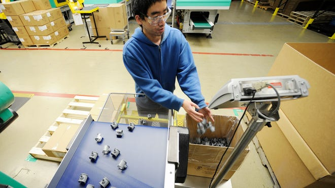 Nha Ziong of Two Rivers transfers injection molded chicken feeder parts into a shipping box in October 2014 at Ironwood Plastics, which is adding technology, manufacturing space and, in 2015, will start doubling the size of its workforce.