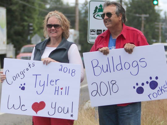 Jennifer Smith and Brian Seaberg hold signs supporting Smith's son, Tyler Hill, during the Slow Day parade for graduating seniors at North Mason High School.