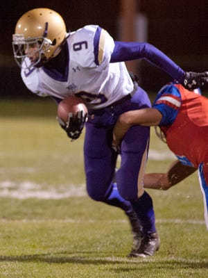 Male Bulldogs wide receiver Zackery Smith tries to evade the grasp of Christian Academy of Louisville Centurions defensive back Cal Lewellyn.31 October 2015