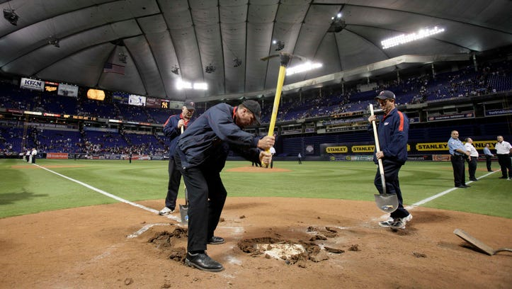 Workers mark the final Twins game at the Metrodome by digging up home plate after a 2009 AL Division Series loss to the Yankees.