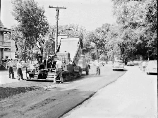 Historic photo of men paving a Vermont road.