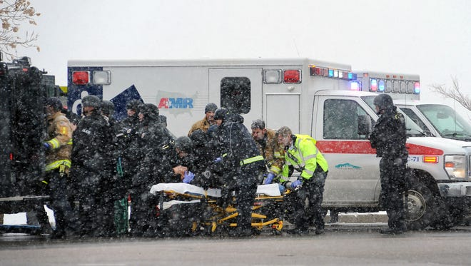 Emergency personnel transport an officer to an ambulance after reports of a shooting near the Planned Parenthood clinic Friday, Nov, 27, 2015, in Colorado Springs, Colo.
