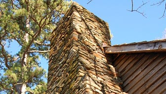 A rock chimney on the side of an old house.