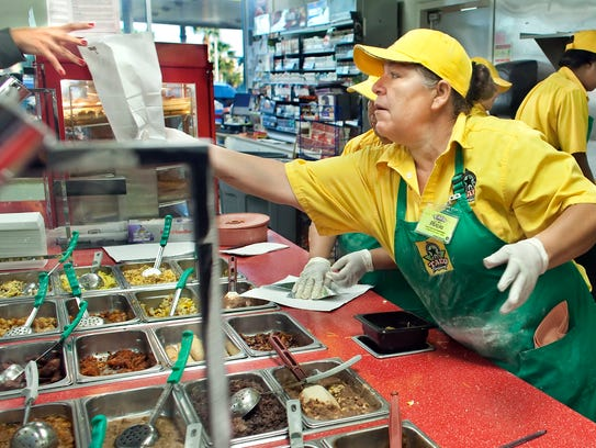 Alicia Martinez hands a breakfast tacos to a customer