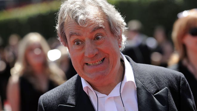 """FILE - In this Saturday, Aug. 21, 2010 file photo, Terry Jones arrives at the Creative Arts Emmy Awards in Los Angeles. Terry Jones, a member of the Monty Python comedy troupe, has died at 77. Jones's agent says he died Tuesday Jan. 21, 2020. In a statement, his family said he died """"after a long, extremely brave but always good humored battle with a rare form of dementia, FTD."""""""