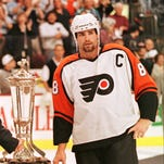 Philadelphia Flyers Eric Lindros stands next to the Prince of Wales Trophy after the Flyers won the Eastern Conference Finals in 1997.