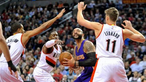 Portland Trail Blazers' CJ McCollum, left, Wesley Matthews (2) and Meyers Leonard (11) defend against Los Angeles Lakers' Carlos Boozer during the first half of an NBA basketball game in Portland, Wednesday Feb. 11, 2015.